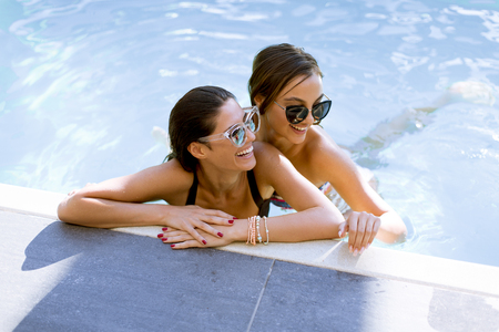 Two beautiful young Women with sunglasses relaxing together by poolside of outdoor swimming pool and smiling