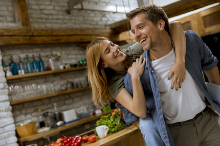 Lovely young couple having fun together at rustic kitchen
