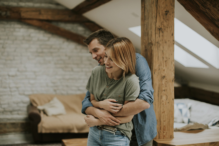 Young man and woman hugging standing at home interior and tender husband embracing wife gently Stock Photo