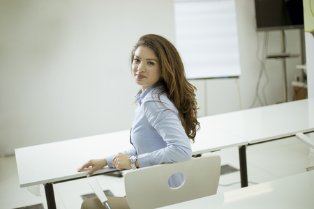 Beautiful young female student sitting on a chair and turning back in the classroom Stock Photo