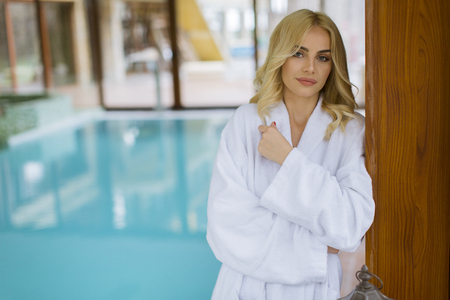 Beautiful young blonde woman in bathrobe relaxing at indoor swimming pool Imagens