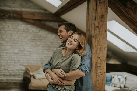 Young man and woman hugging standing at home interior and tender husband embracing wife gently 스톡 콘텐츠