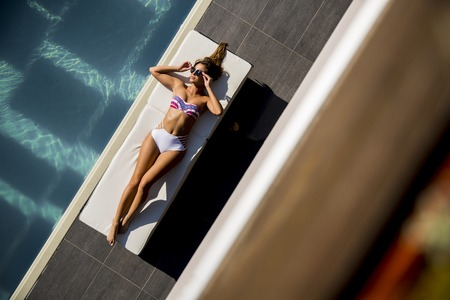 Over view at beautiful tanned woman with sunglasses in bikini relaxing near luxury swimming pool