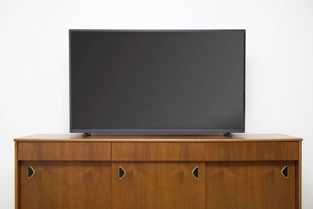 Modern TV set with empty blank screen on the wooden cabinet in front of white wall Banque d'images - 124567855