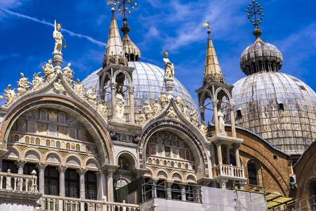 Architectural details from the upper part of facade of San Marco in Venice, Italy under blue sky