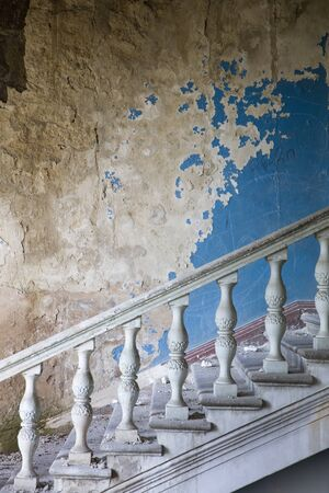 Side view at old staircase in interior of an abandoned and ruined building Banco de Imagens