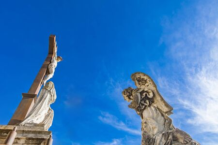 Angel sculpture at front of Avignon cathedral of Our Lady of Doms in France, under statue of Jesus Christ Stock Photo