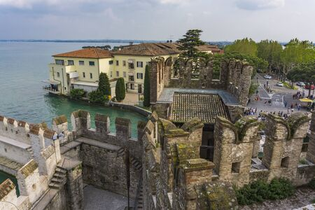 SIRMIONE, ITALY - MAY 24, 2019: View at town Sirmione from Scaligero Castle in Italy. Castle is a fortress from the Scaliger era built in 13th century.