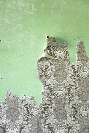 Detail of the torn wallpapers on the old green wall Imagens
