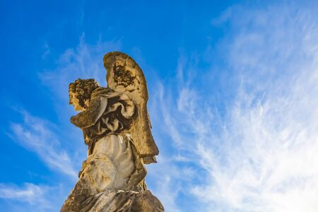 Angel sculpture at front of Avignon cathedral of Our Lady of Doms in France, under clear blue sky