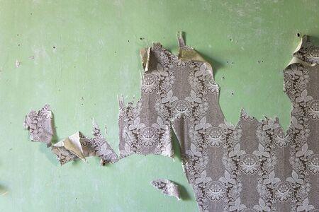 Détail des papiers peints déchirés sur le vieux mur vert