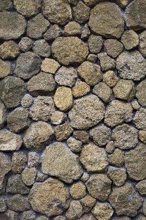 Texture backdrop of an old stone wall from uneven different ancient stones of various forms