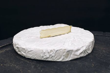 Brie cheese on black background