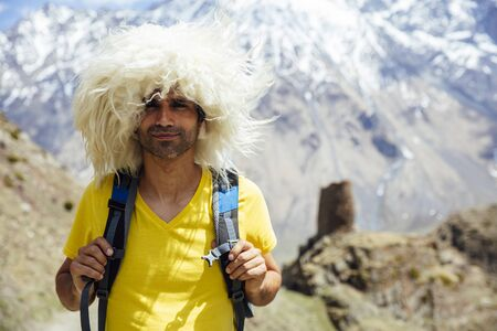 View at young hiker with traditional papakha fur hat at high latitude mountains at Mtskheta-Mtianeti region in Georgia Imagens