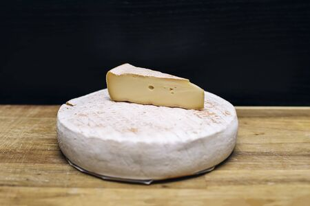 Brie cheese on wooden table against black background 스톡 콘텐츠