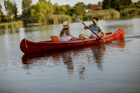 Loving couple rowing on the lake at summer day Banque d'images