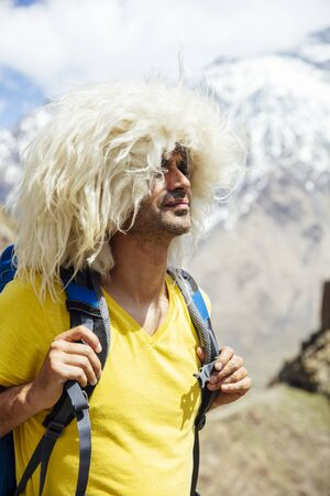 View at young hiker with traditional papakha fur hat at high latitude mountains at Mtskheta-Mtianeti region in Georgia