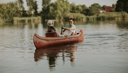 Loving couple rowing on the lake at summer day