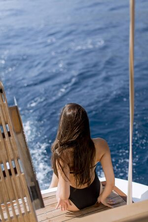 Pretty young woman with sunglasses relaxing on the yacht on sea at sunny day