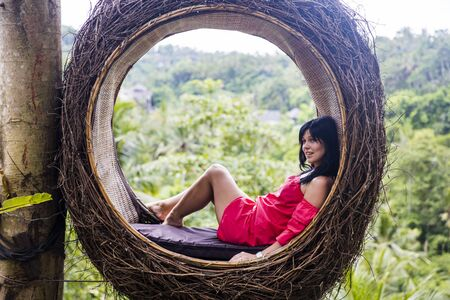 A female tourist is sitting on a large bird nest on a tree at Bali island, Indonesia