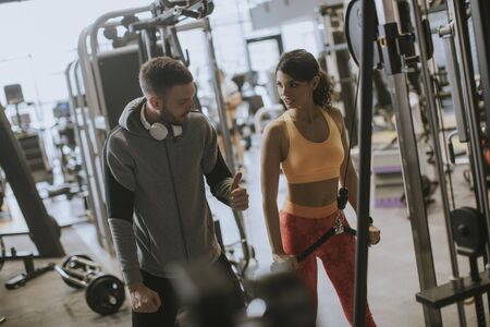 Young pretty sporty woman working out on pull-down machine in gym with personal trainer Stock Photo