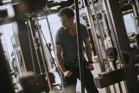 Young handsome sporty man working out on pull-down machine in gym