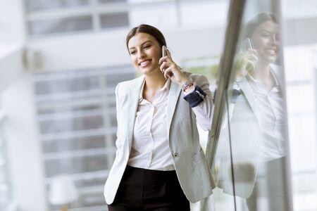 Hübsche junge Geschäftsfrau steht auf der Treppe im modernen Büro und benutzt Handy Standard-Bild