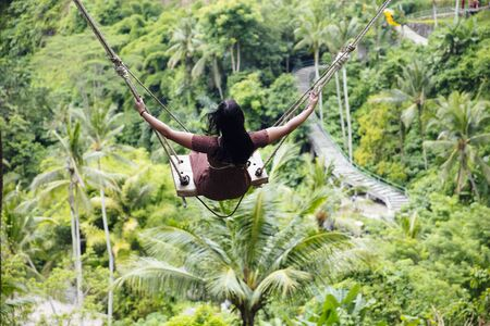 Young tourist woman swinging over the tropical rainforest at Bali island, Indonesia
