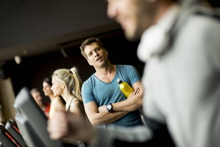 Handsome young man drinking bottle of water on threadmill in gym Stock Photo