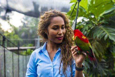 BALI, INDONESIA - JANUARY 25, 2019: Unidentified woman with tropical bird at Bali Bird Park in Indonesia. It is a tourist attraction with more than 250 bird species.