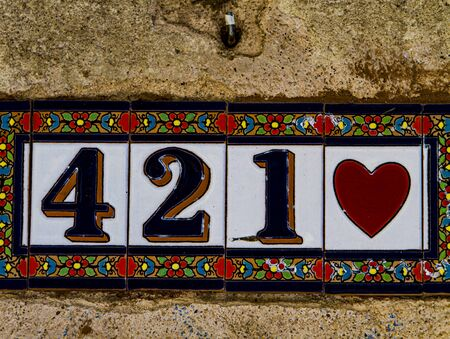 Traditional decorative street number plate from facade of old house in Nimes, France