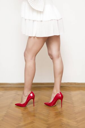 Beautiful female legs with red heels shoes on the floor by the white wall