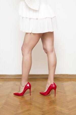Belles jambes féminines avec des chaussures à talons rouges sur le sol près du mur blanc