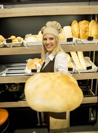 Pretty young woman selling soft  fresh bread in the bakery Фото со стока