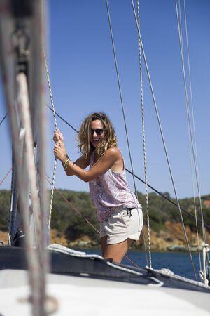 Beautiful young woman traveling along Mediterranean sea on sail boat at summer