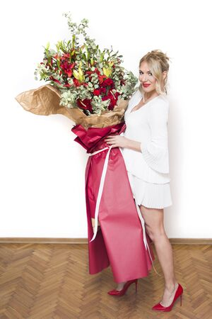 Young beautifull blond woman holding big bouquet of colorful flowers against the white wall 写真素材
