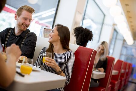 Friends eating and drinking juice at the table in the diner Stock Photo