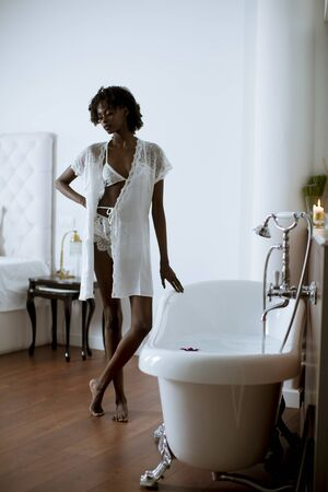 Pretty young african american woman standing by the bathtub in the bathroom