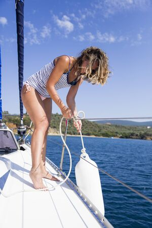 Young attractive woman wants to drop buoys on a sailboat at the hot summer day 免版税图像