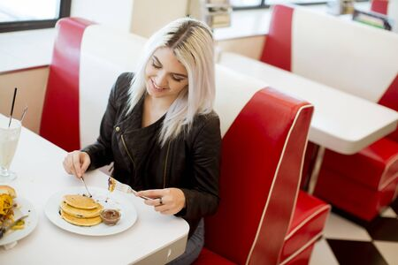 Pretty young woman eating pancakes in the diner