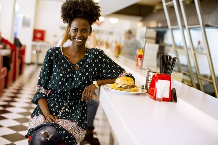Pretty young african american woman sitting in the diner