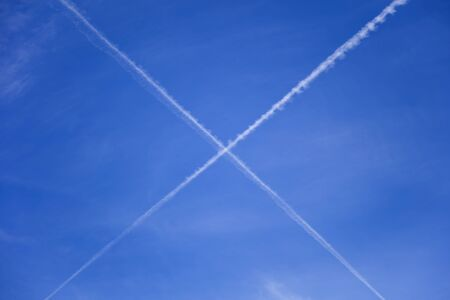 White crossing trace of airplanes in the blue sky