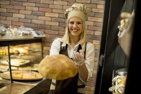 Pretty young woman selling soft  fresh bread in the bakery 版權商用圖片
