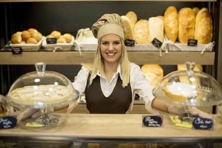Portrait of friendly female baker with fresh bread smiling in bakery