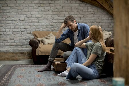 Young couple sitting in the room with a problem, he is upset while she try to confort him Reklamní fotografie