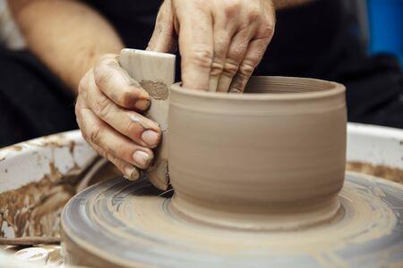 Gros plan sur une vue détaillée d'un artiste par courrier fait de la poterie en argile sur une roue tournante