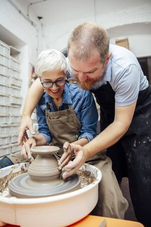 Senior woman spinning clay on a wheel with a help of a teacher at pottery class
