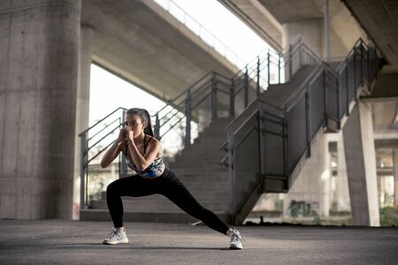 Pretty young woman exercise in urban environment