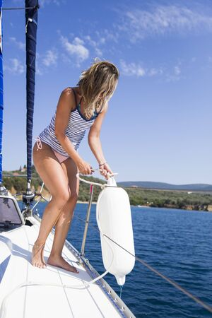 Young attractive woman wants to drop buoys on a sailboat at the hot summer day Stock Photo