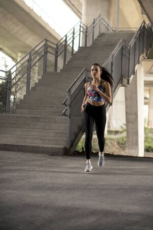 Young woman exercise in urban environment by day
